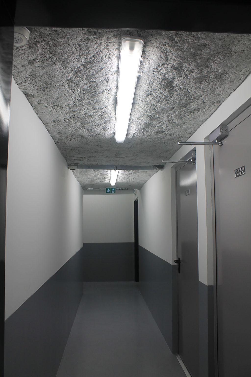 Éclairage et signalétique lumineuse d'évacuation d'un sous-sol.